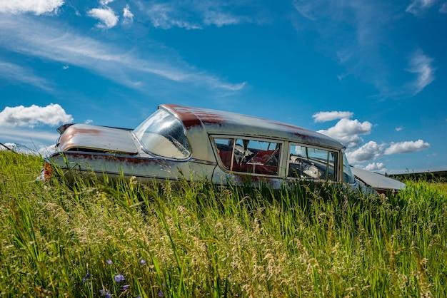 Berline bleue antique abandonnée dans les hautes herbes sur une colline