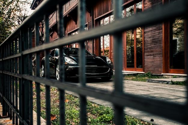 Berline de sport, couleur noire devant un immeuble, vue de face à travers un autre.