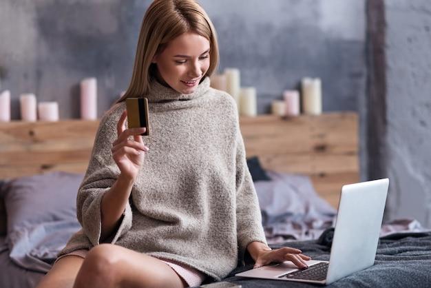 Besoin de le faire. jolie jeune femme ravie de payer les factures et d'utiliser un ordinateur portable tout en tenant la carte de crédit dans la chambre.