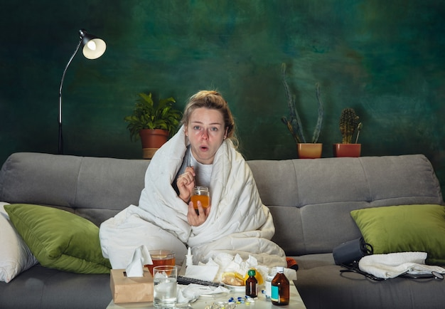 Besoin d'un médicament. jeune fille malade avec fièvre et froid se sentant malade, bleu, reniflant. semble souffrant et faible, couvrant d'enveloppe. rhume, virus, grippe saisonnière. femme assise sur un canapé à la maison.