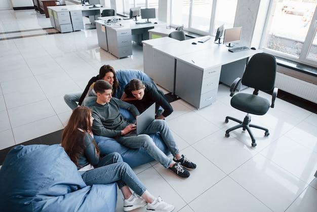 Besoin de regarder de plus près. groupe de jeunes en vêtements décontractés travaillant dans le bureau moderne