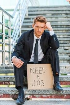 Besoin d'un travail. jeune homme déprimé en tenue de soirée tenant une affiche avec un message texte d'emploi alors qu'il était assis dans l'escalier