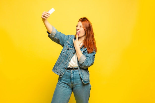 Besoin de vêtements minimum pour selfie. portrait de femme caucasienne sur espace jaune