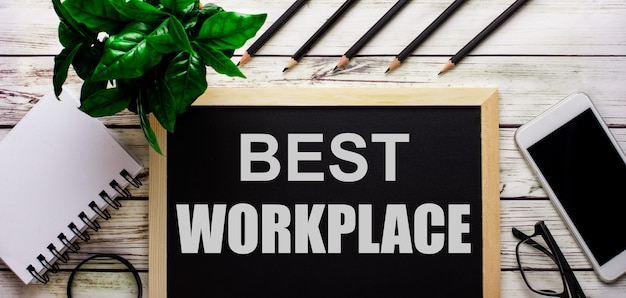 Best workplace est écrit en blanc sur un tableau noir à côté d'un téléphone, d'un bloc-notes, de lunettes, de crayons et d'une plante verte.