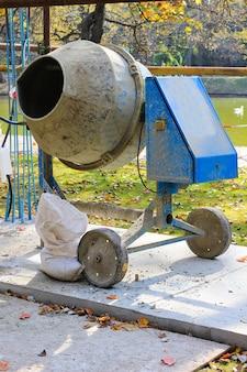 Bétonnière et un sac de ciment sur la piste dans le parc