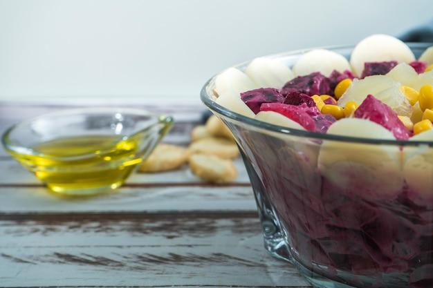 Betterave ananas maïs coeurs de palmier et salade de chicorée à l'huile d'olive et basilic dans un bol en verre
