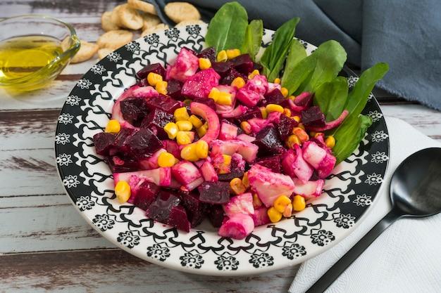 Betterave ananas maïs et salade de chicorée à l'huile d'olive et basilic sur une assiette sur une table rustique en alambic
