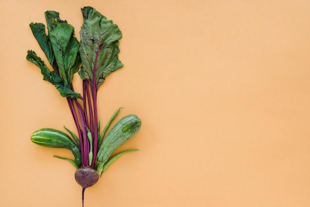 Betterave décorative avec des feuilles; haricots verts; concombre et courgette sur fond brun