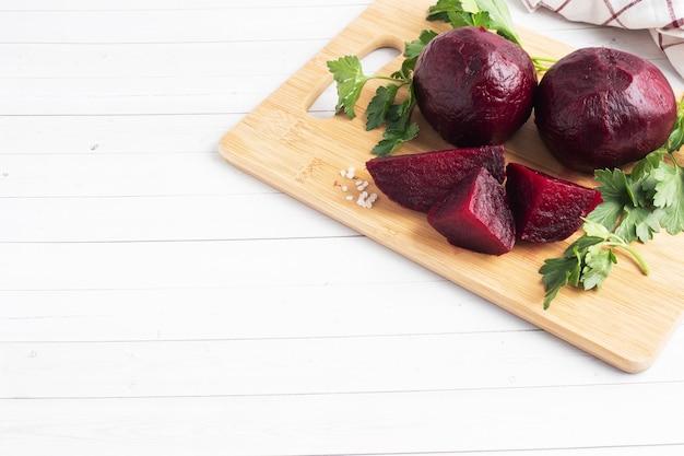 Betteraves bouillies entières et coupées sur une planche à découper avec des feuilles de persil sur fond blanc