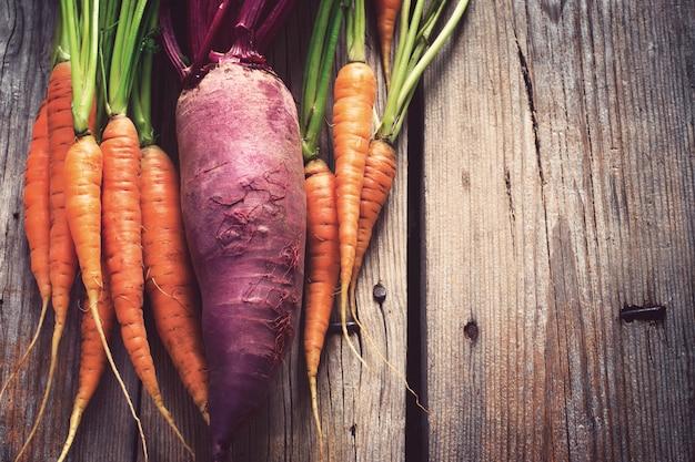 Betteraves et carottes biologiques fraîches sur des planches en bois