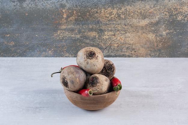 Betteraves crues et piments dans un bol en bois. photo de haute qualité