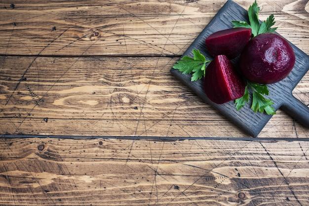 Betteraves cuites entières et coupées sur une planche à découper avec des feuilles de persil sur un fond rustique en bois.