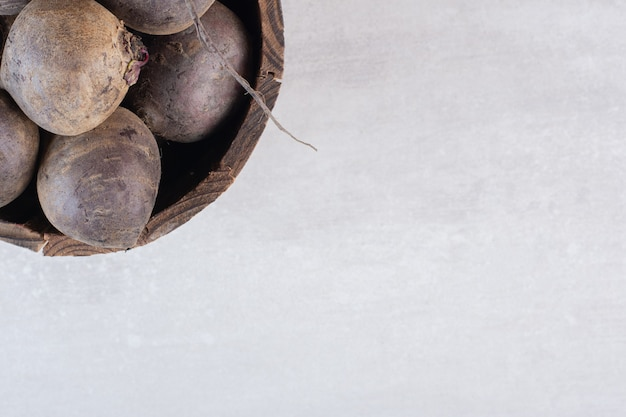 Betteraves fraîches crues dans un seau en bois. photo de haute qualité