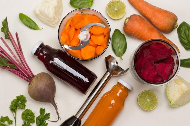 Betteraves hachées dans un bocal, carottes hachées dans un bocal mélangeur. betteraves avec dessus et carottes non pelées. broyeur de métaux. chou et moitiés de citron, basilic et persil. mise à plat. fond blanc. copier l'espace