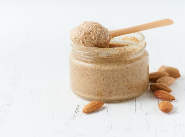 Beurre d'amande, pâte d'aliments crus à base d'amandes broyantes, bocal en verre, vue latérale, gros plan, espace copie
