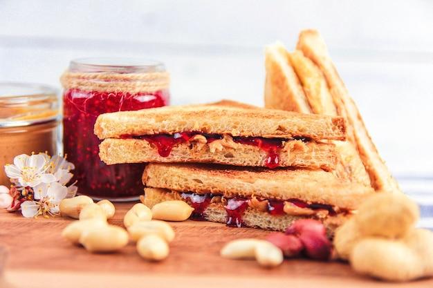 Beurre d'arachide et confiture de framboises près de cacahuètes et sandwichs