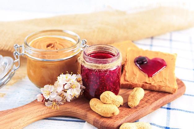 Beurre d'arachide et confiture de framboises près de cacahuètes