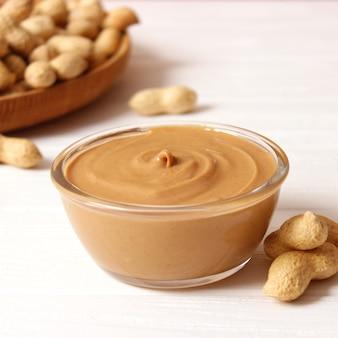 Beurre d'arachide crémeux et haricots d'arachide sur la vue de dessus de fond en bois. photo de haute qualité