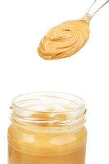 Beurre d'arachide crémeux en pot, isolé sur blanc