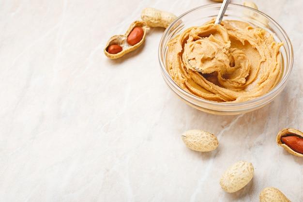 Beurre d'arachide dans une assiette en verre avec des arachides en coque, des arachides décortiquées, une cuillère avec du beurre d'arachide.