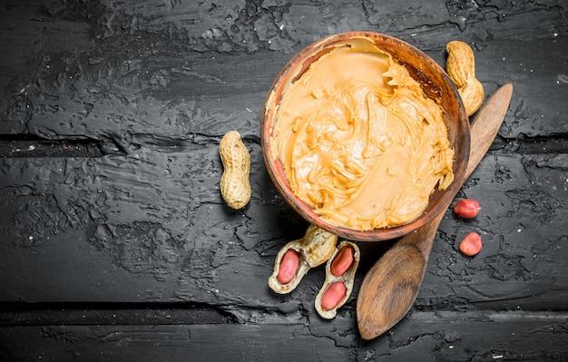 Beurre d'arachide dans un bol avec une cuillère en bois. sur fond rustique noir.