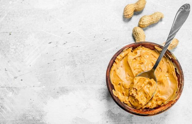 Beurre d'arachide dans le bol. sur un fond rustique.