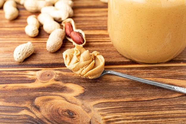 Beurre d'arachide dans une cuillère près de pâte d'arachide crémeuse dans un bocal en verre ouvert. arachides sur table en bois.