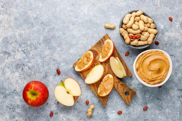 Beurre d'arachide fait maison avec des arachides sur une table en béton gris, vue du dessus