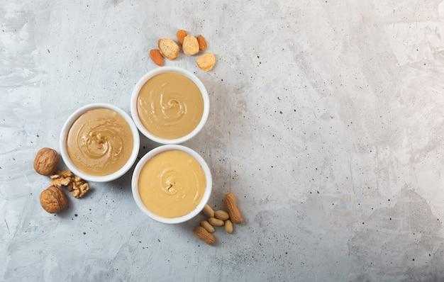 Beurre d'arachide, de noix et d'amande sur la table grise, vue du dessus, copiez l'espace