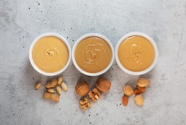 Beurre d'arachide, de noix et d'amande sur la table grise