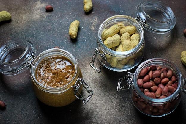 Beurre de cacahuète dans un bocal et cacahuètes dans un bocal