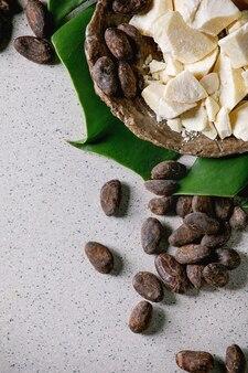 Beurre de cacao haché sur un bol et feuille de monstera