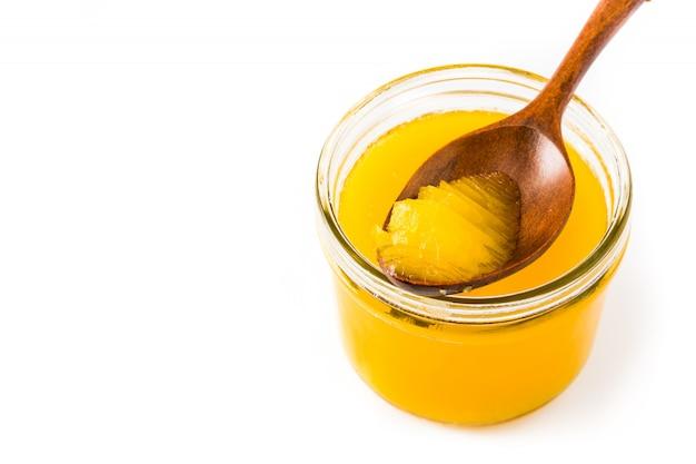 Beurre clarifié en pot et cuillère en bois isolé