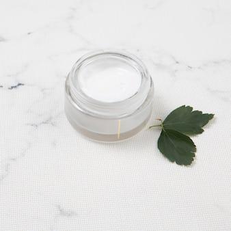 Beurre corporel avec des feuilles sur fond de marbre