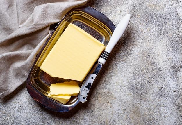 Beurre frais et couteau dans un beurrier