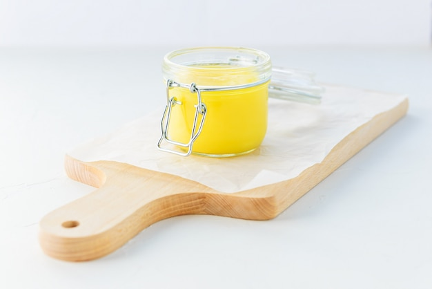 Beurre de ghee dans un pot sur une planche de bois.