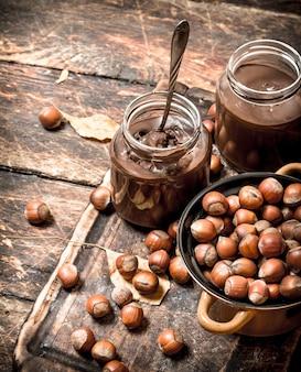 Beurre de noix au chocolat et noisettes sur fond de bois