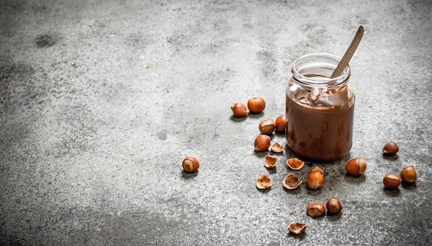 Beurre de noix de noisettes et chocolat sur fond rustique