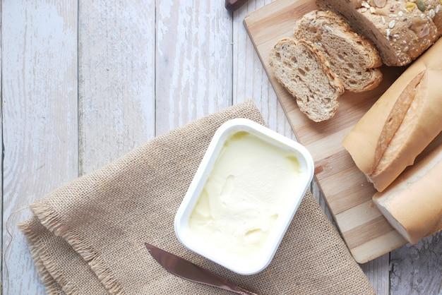 Beurre en récipient et repas entier élevés sur table
