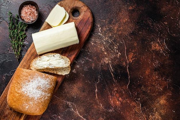 Beurre à tartiner et toasts de denrées alimentaires sur une planche à découper en bois