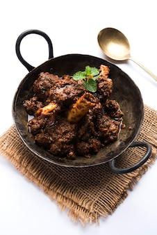 Bhuna gosht mutton masala ou curry d'agneau indien servi dans un bol sur fond de mauvaise humeur. mise au point sélective