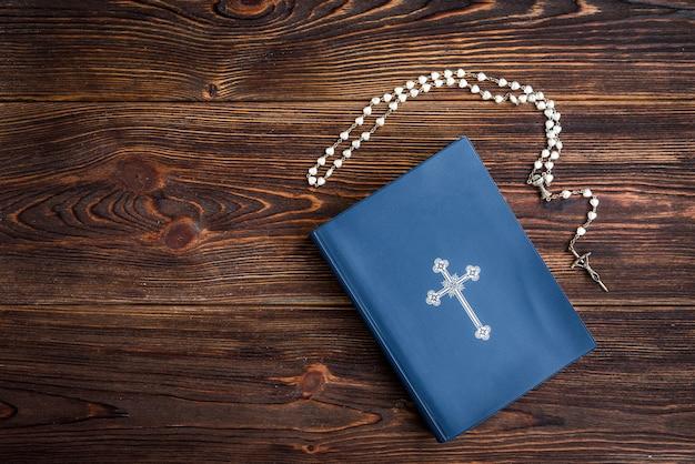 Bible ouverte, bougie, croix chrétienne et mains humaines sur bois