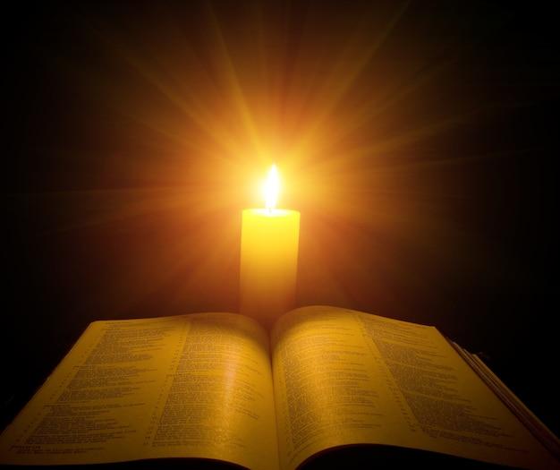 Une bible ouverte sur une table à côté d'une bougie