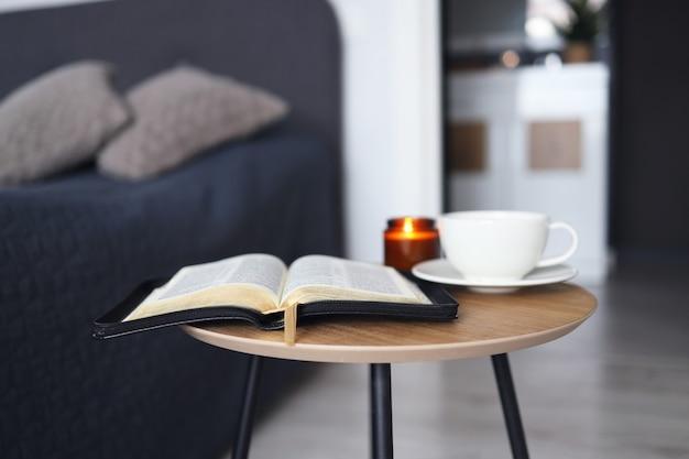 Bible ouverte avec une tasse de thé et des bougies sur une table en bois dans la chambre. l'heure de la prière.