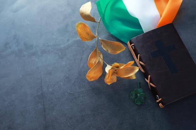 Une bible reliée en cuir sur la table. célébration religieuse chrétienne irlandaise. trèfle à quatre feuilles symbole de bonne chance.