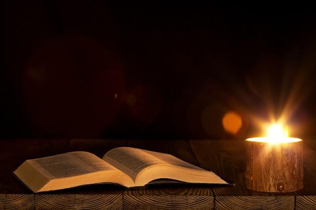 Bible sur la table à la lumière d'une bougie