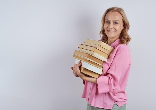 Bibliothécaire enseignante souriante en chemise rose tenant une pile de livres à la recherche. notion d'apprentissage