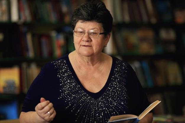 La bibliothécaire garde le livre dans ses mains contre la surface des étagères