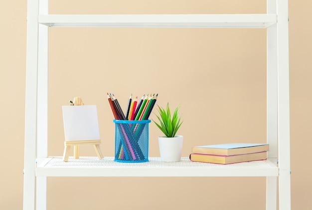 Bibliothèque blanche avec des livres et papeterie contre un mur beige