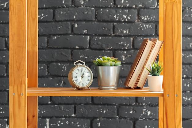Bibliothèque en bois avec des livres et des trucs contre le mur de briques noires